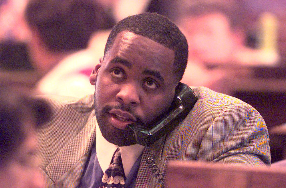 State representative Kwame Kilpatrick talks on the phone while watching the vote board during a session of the Michigan House of Representatives in March 1999.  Courtesy of the Detroit Free Press.