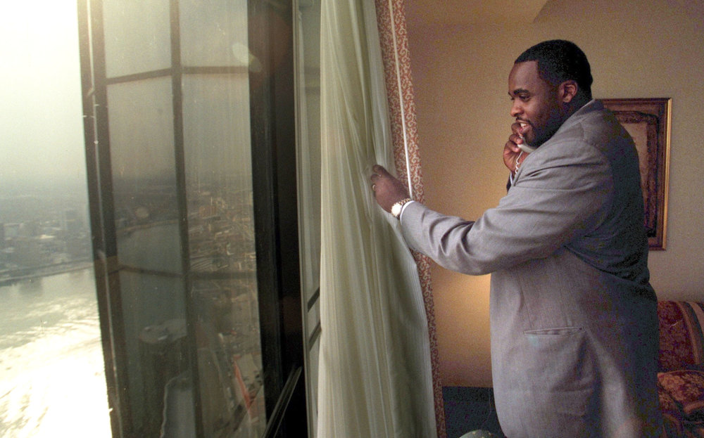 The day after he was elected mayor, Kwame Kilpatrick looks out the window of his 65th-floor suite at the Marriott Renaissance Center while fielding a congratulatory call.  Courtesy of the Detroit Free Press.