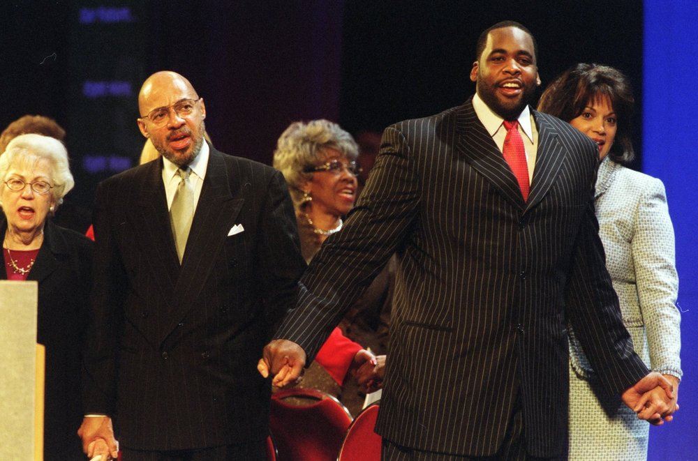 "At Kwame's inauguration ceremony in 2002, outgoing Detroit mayor Dennis Archer and the members of City Council joined him to sing ""Together We Stand.""  Courtesy of the Detroit Free Press."