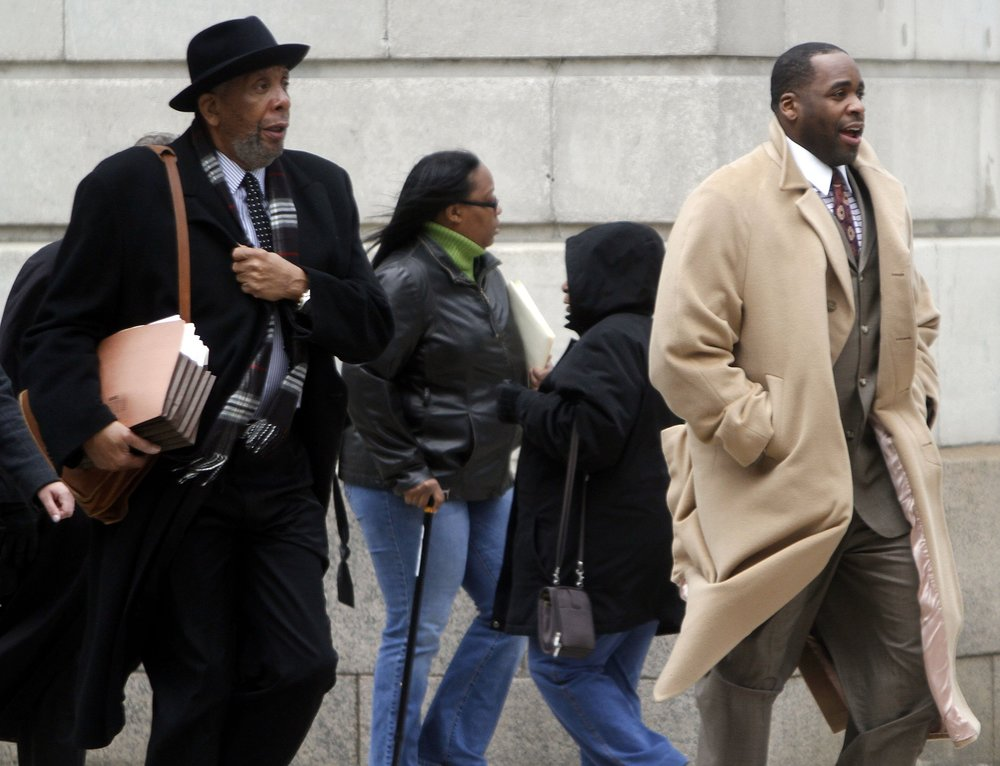 Bernard Kilpatrick, left, and his son Kwame make their way to federal court in Detroit. They were both charged by the federal government with breaking a law originally enacted to go after mob bosses: the Racketeering Influenced and Corrupt Organizations Act.  Courtesy of the Detroit Free Press.