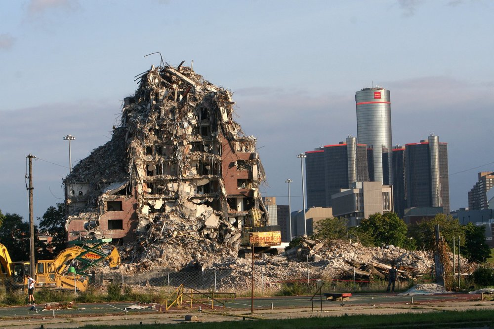 One of the towers of the Brewster-Douglass Housing Projects is demolished in 2014, with the Renaissance Center looming in the background. Plans were made for the former public housing site to be redeveloped by a partnership including billionaire Dan Gilbert, who has played a role in many real estate projects in downtown Detroit.  Courtesy of the Detroit Free Press.