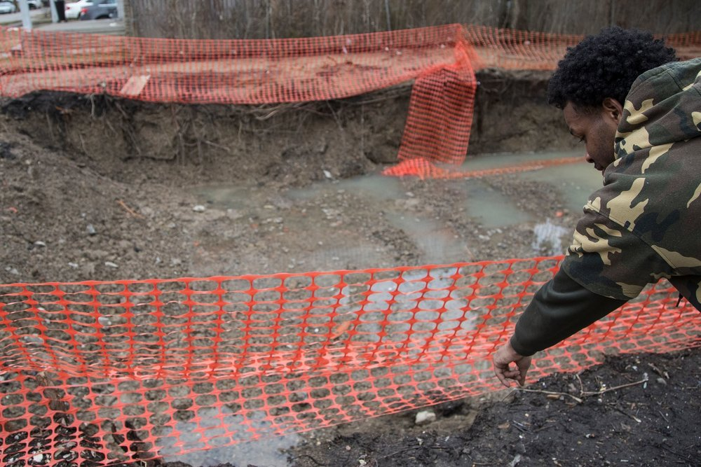 Demolition pits have become a public safety hazard and a symbol of Detroit's troubled demolition program. Derrick Pratt, a resident on Auburn Street, points out where he slipped into a hole next to his house in February 2019.  Courtesy of the Detroit Free Press.