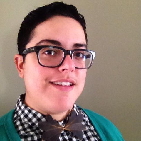 [Image description: an olive-skinned person with short black hair and black glasses looks at the camera at an an gle. They are smiling slightly. They wear a black-and-white checkered shirt, a green cardigan, and a bowtie made out of wood, which has a botanical look]