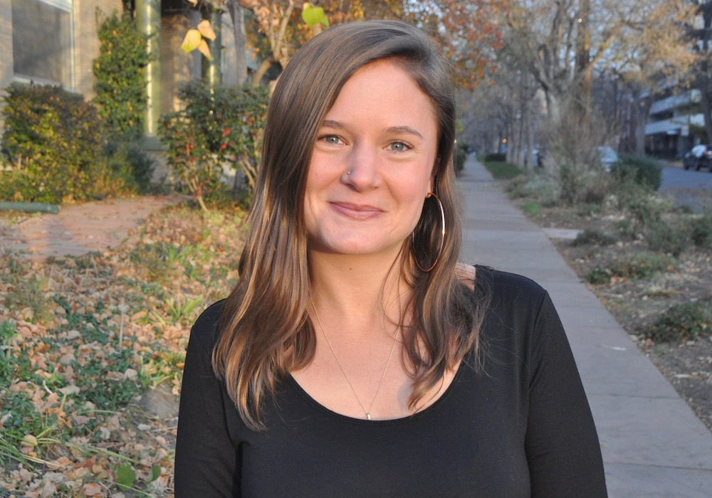[Image description: a white person with shoulder-length brown hair, hoop earrings, a necklace, and a black shirt smiles at the camera. The background is a tree-lined sidewalk.]