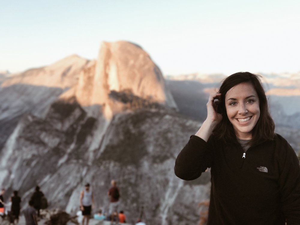 [Image description: a light-skinned person with shoulder-length brown hair smiles at the camera while touching her hair. She is wearing a black shirt. In the background, the top of a rocky mountain is visible, as well as a few other hikers]