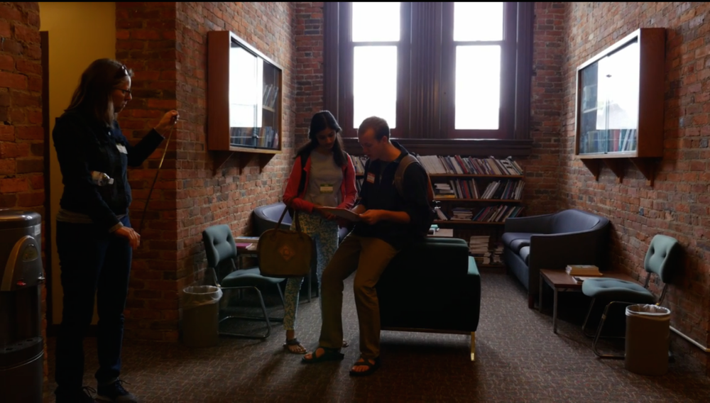 [Image description: a faculty member and two students survey a campus building for accessibility. One person holds a measuring tape and two others look at the survey text while leaning against chairs in a brightly-lit nook]