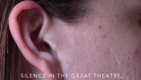 "[Image description: screenshot of video by author featuring a cropped image of the profile view of a face and ear. White text overlaying the image says: ""Silence in the great theatre,"""