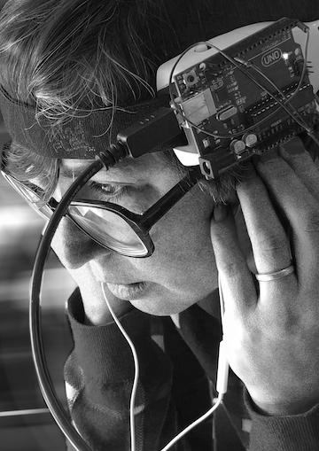 Image description: A person with short brown hair and glasses tilts their head downwards as they look off-screen. They are wearing an Arduino on a headband, their hands hold a pair of earbuds in their ears, and multiple wires extend downwards, out of the image. The image is grainy black & white, with the background blurred to remove extraneous information.