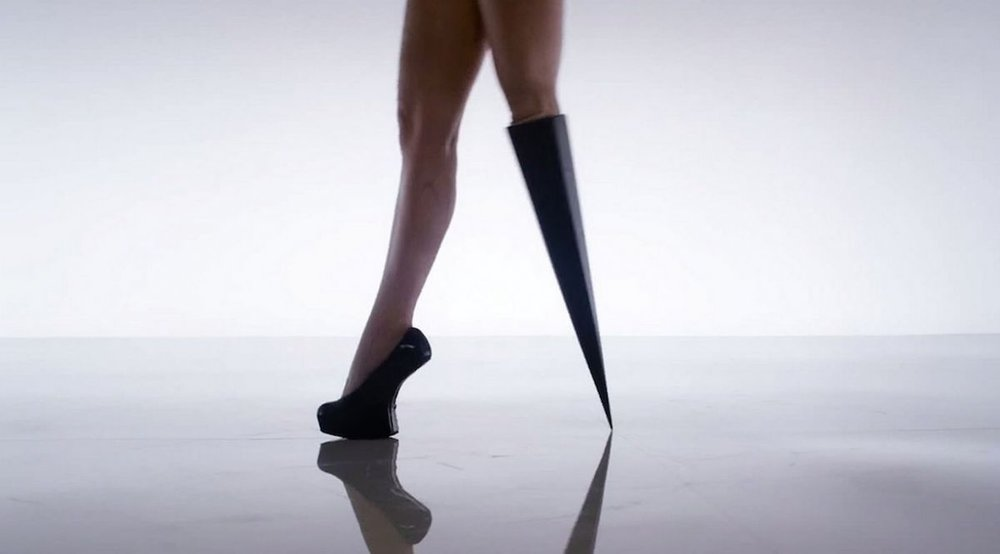 Image description: Pop star Victoria modesta's legs: one leg wears a black high-heeled shoe. The other, a cone-shaped black prosthetic, which comes to a single point at the floor.  Source:  Futurism.com