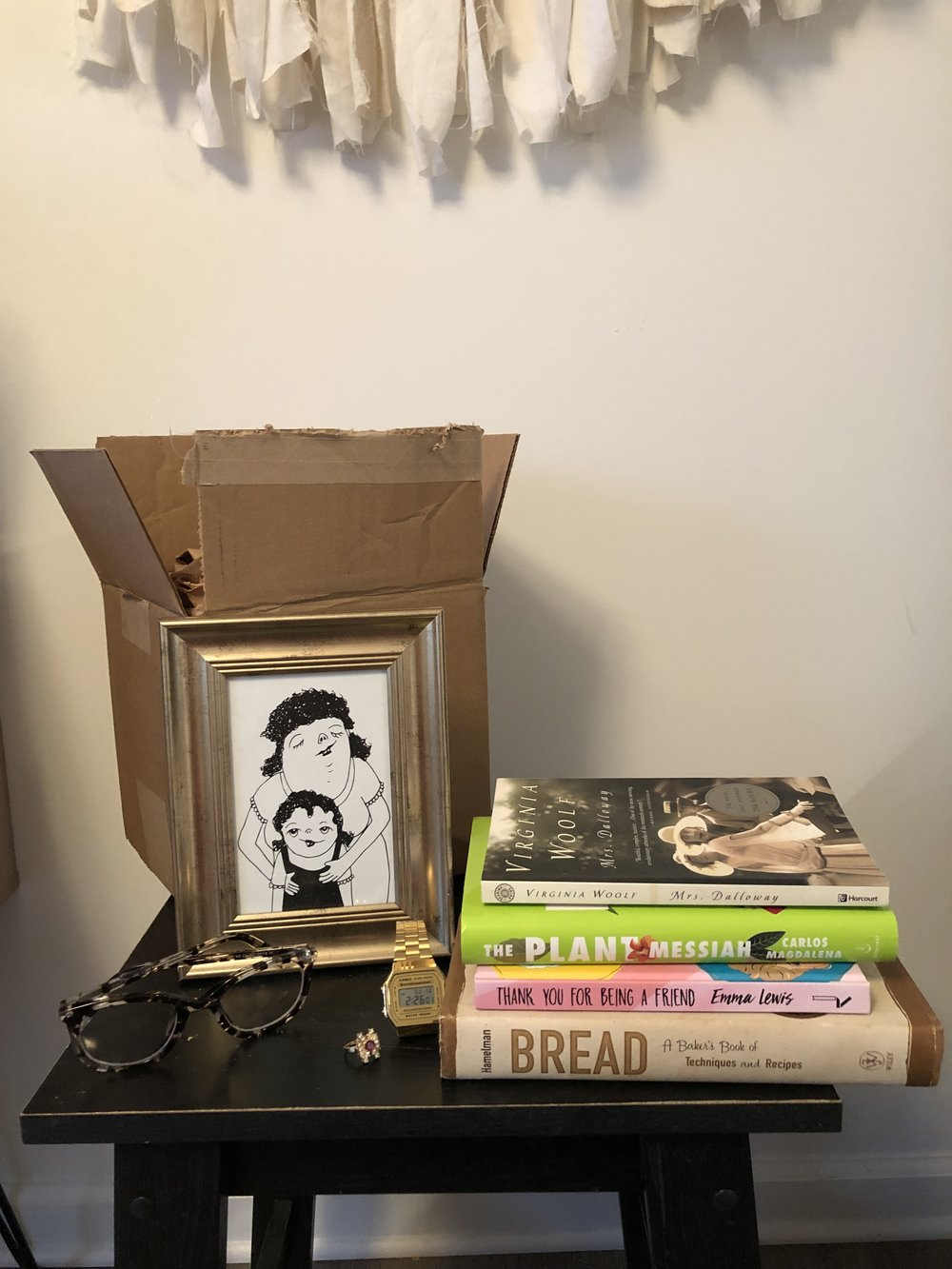 Image description: A stack of books, a pair of glasses, a ring, a watch, and a drawing sit on a chair in front of an open cardboard box, indicating sentimental objects included in one Home in a Box.