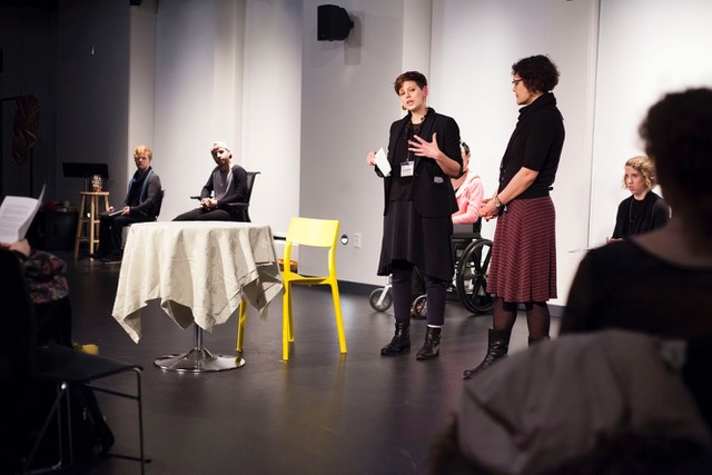 Image description: At a staged reading of the play at Yale CCAM, March 2018. Cassandra Hartblay and Director Elise Morrison introduce the piece. Actors are seated in the background.
