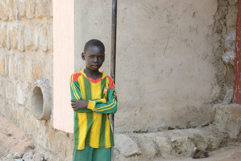 A child poses wearing the red, yellow, and green Ethiopian National Soccer Team jersey