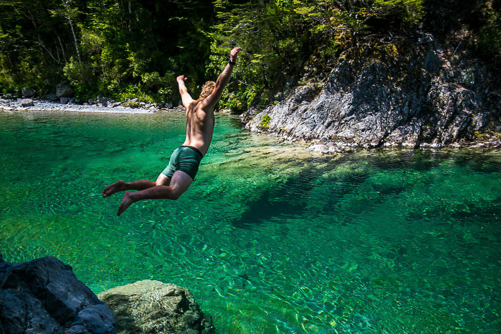 Sam does a belly flop into the crystal clear waters along the Te Araroa trail in New Zealand