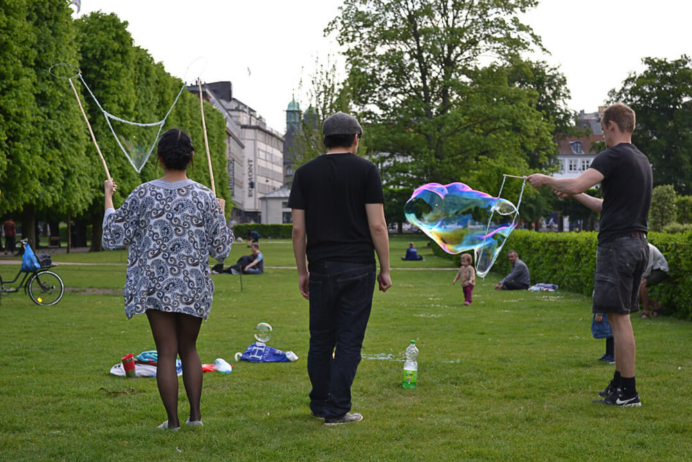A couple plays with bubbles in the Danish royal gardens