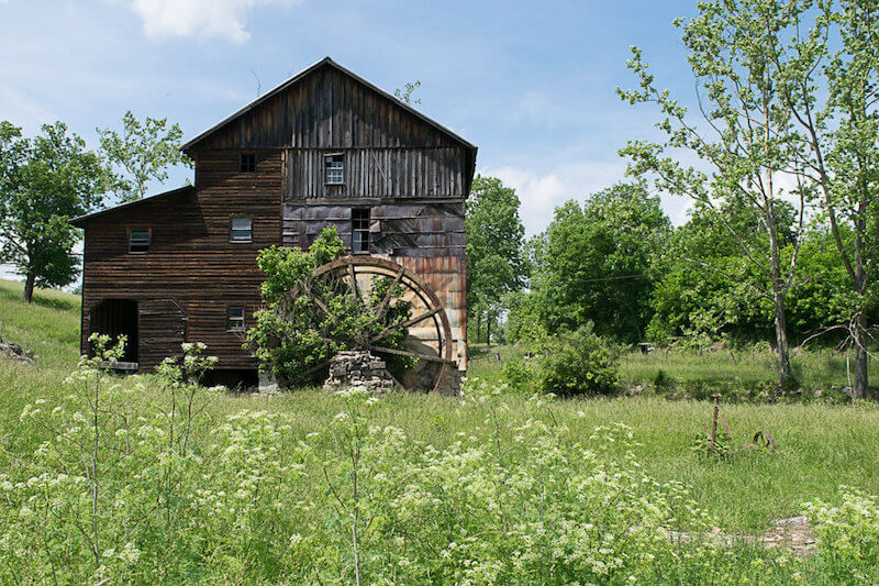 An abandoned watermill along the side of the road