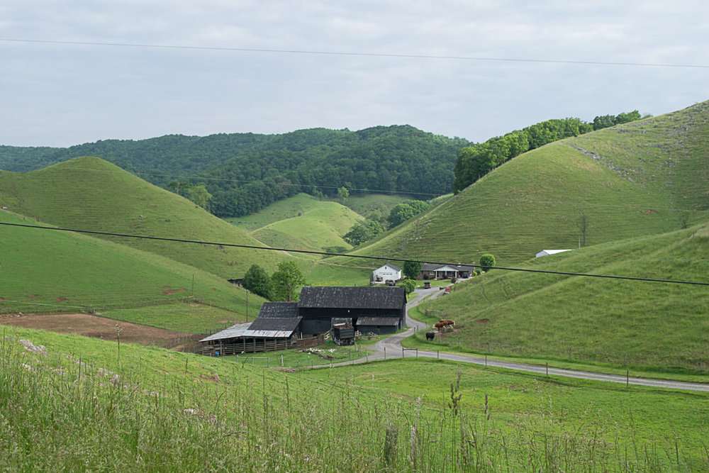 A farm sits at the valley of rolling hills
