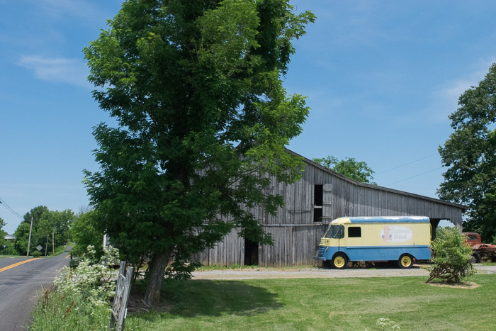 A bread truck sits outside an old wooden farm