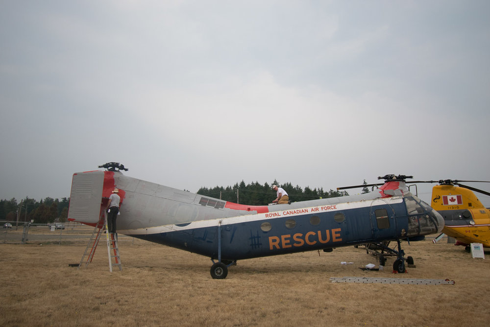 Veterans at Comox Airport Museum paint a helicopter from WWII