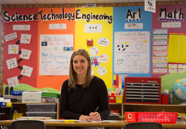 Camille Jones, 2017 Washington State Teacher of the Year. At teacher's desk, with STEAM backdrop.