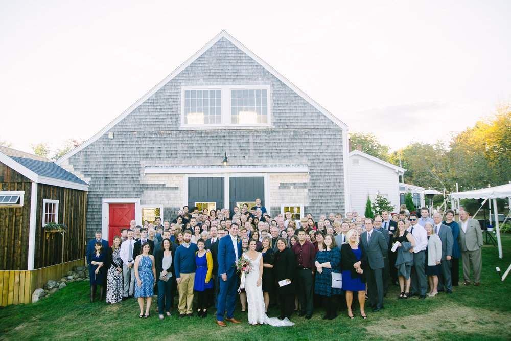 wedding guests gather behind barn outdoors