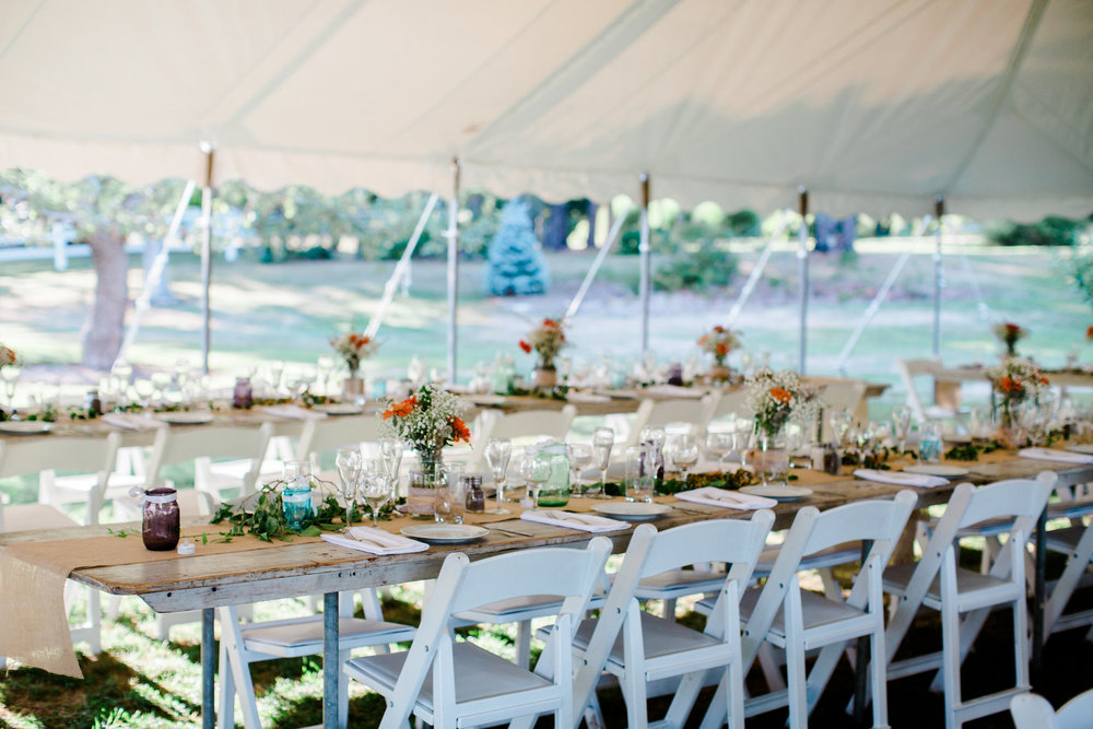 farm tables under tent for outdoor reception