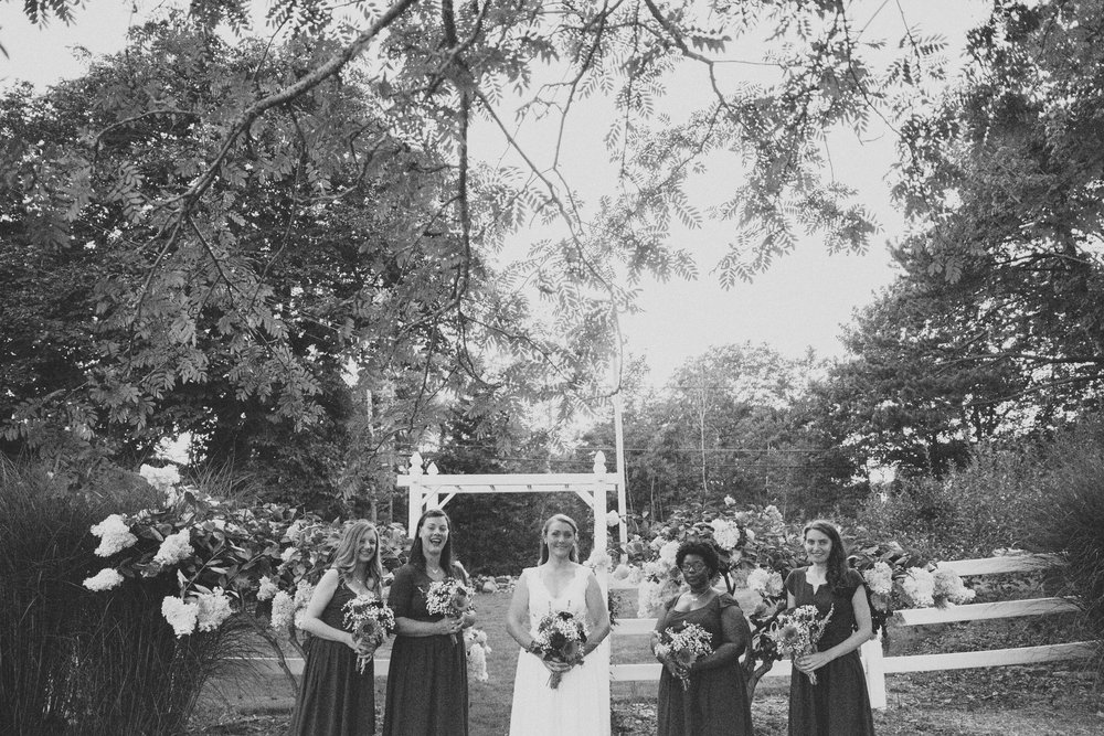 bride with bridesmaids under garden arbor