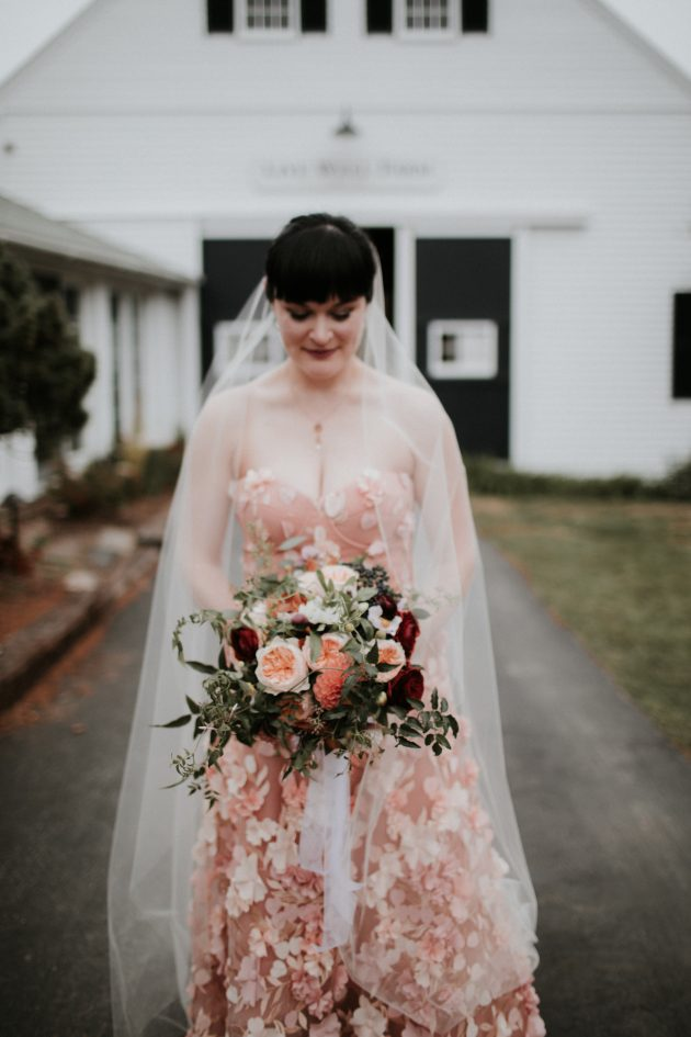 outdoor bride in pink gown with fall floral arrangement