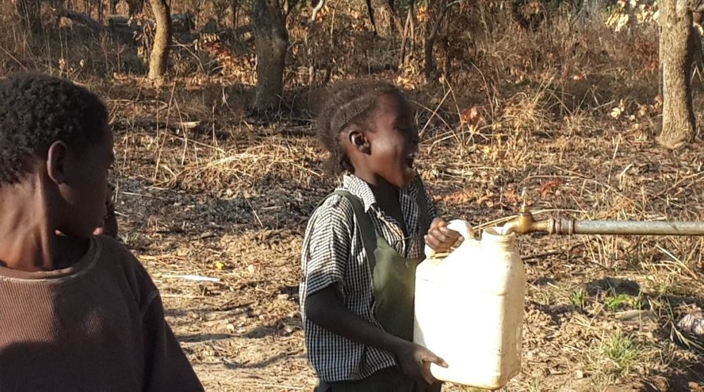 - Children Drinking Clean Water Made from a Borehole as Part of the Forestry Project