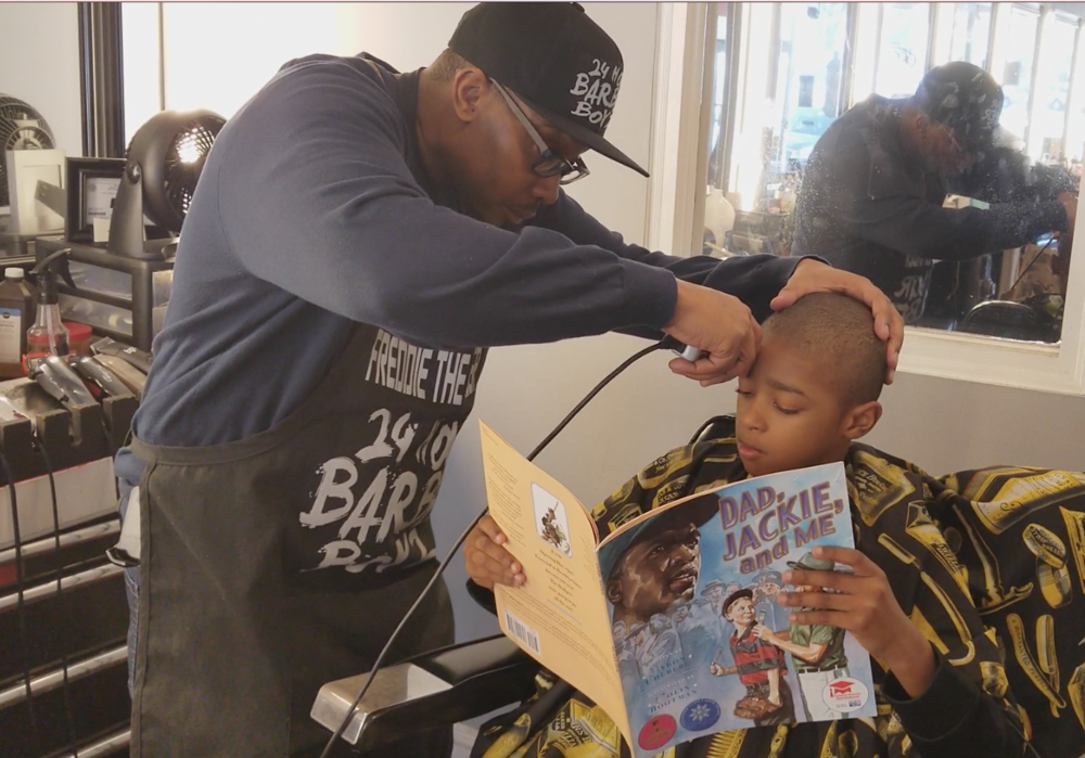 Real Dads Read Barbershop partner Freddie Johnson, III reading with Kenneth Braswell Jr. at Anytime Cutz in Atlanta.