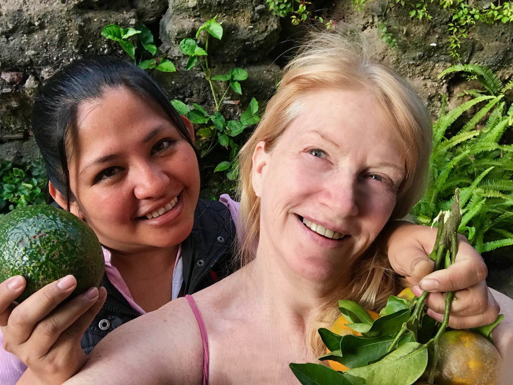 Friends Antonia and Sherrlyn in Guatemala with an avocado and tangerines.