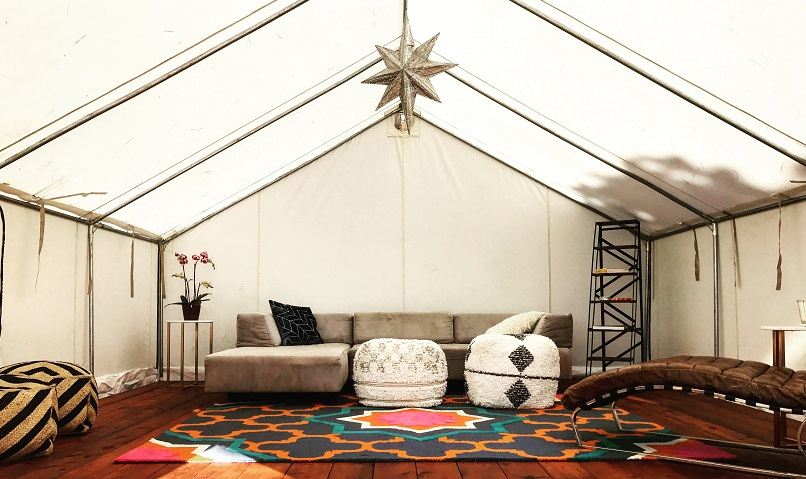 Lounge Tent-  Beautifully designed glamping lounge with couches, seating areas, rugs and a bookshelf stocked with games, books and cards