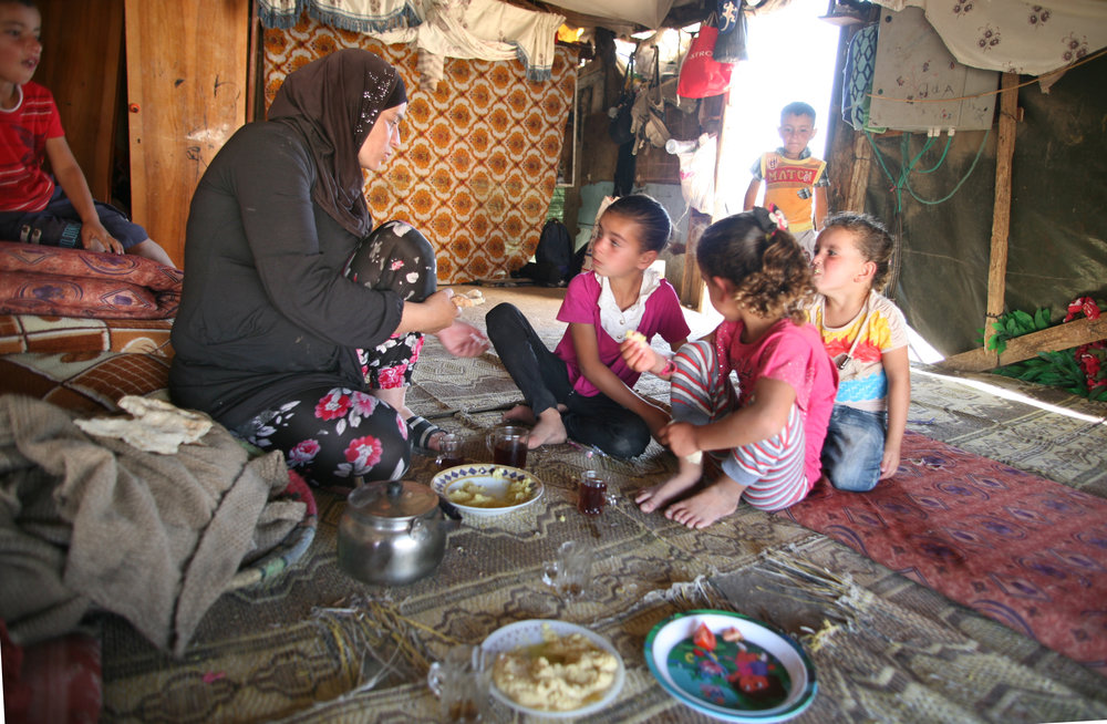 A pregnant young mother and her five children sit down to eat what is left from   from their guests' leftovers.