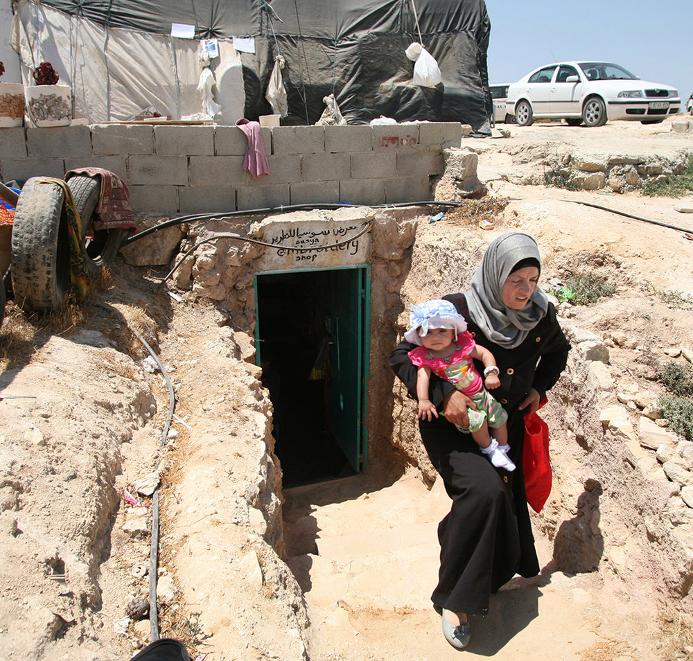 Susiya mother Haleem and her baby daughter, Sura, leave the Embroidery Shop in a hand-dug cave at the center of the village of tents.
