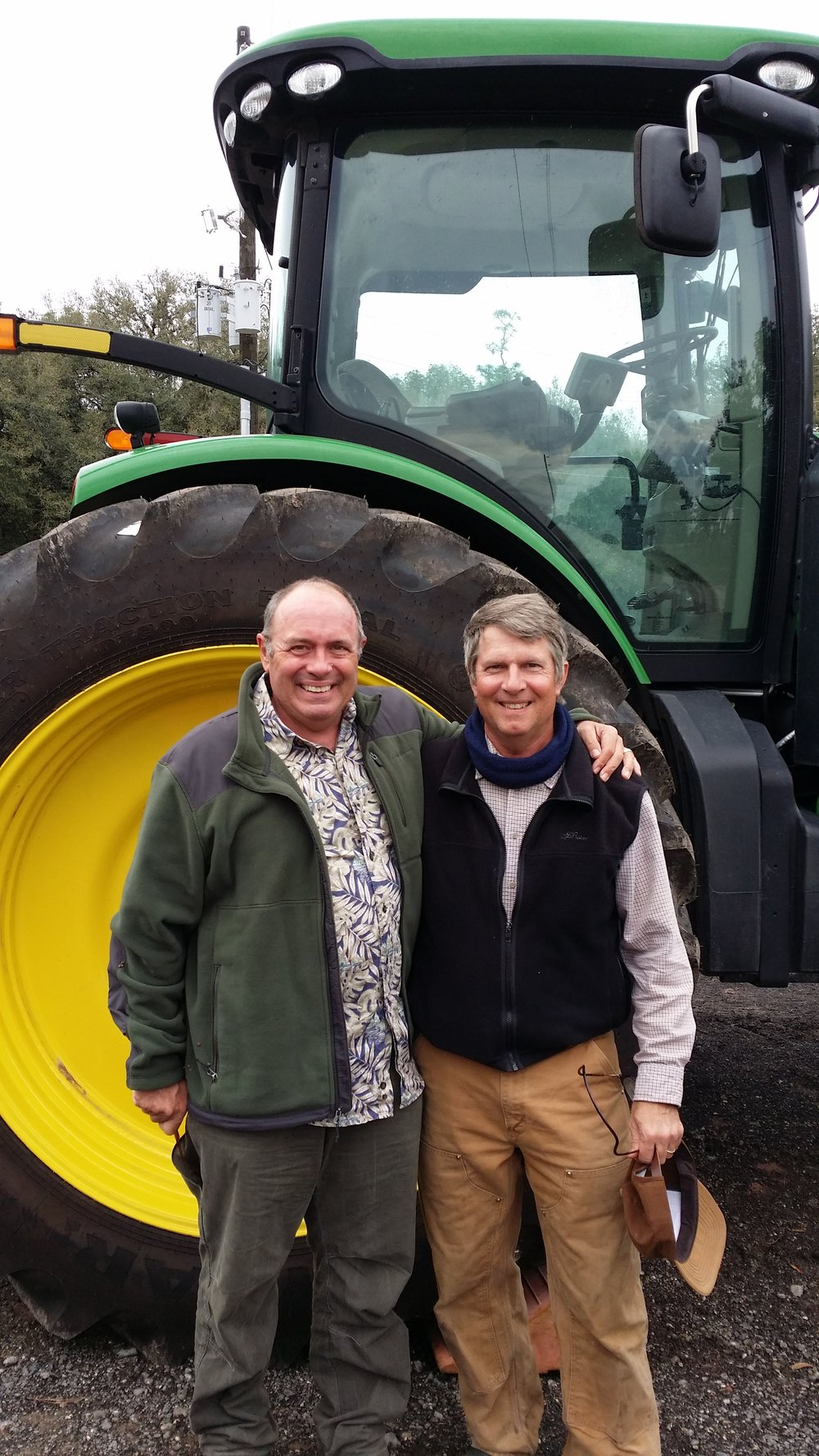 Leonard Park and Birge Sigety in front of a new tractor at the farm.