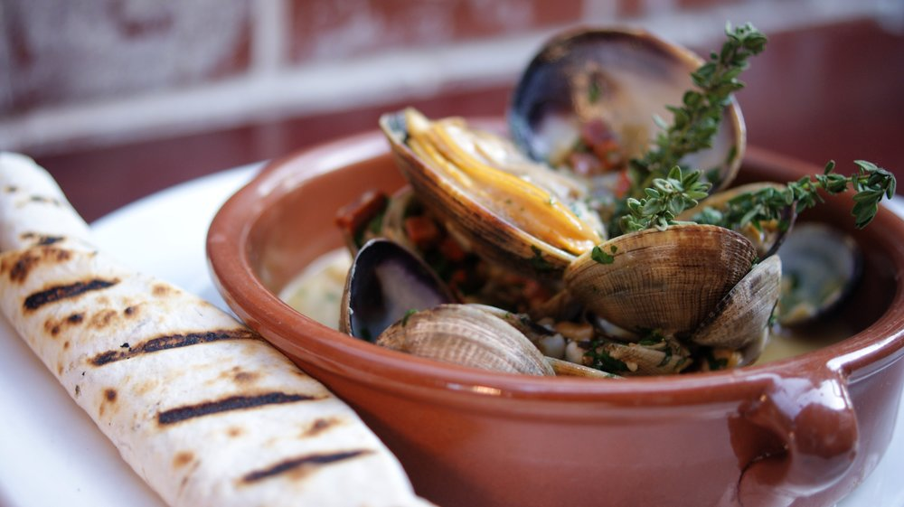 Brown Manilla Clams Served In Red Ceramic Dish With Tortilla On The Side
