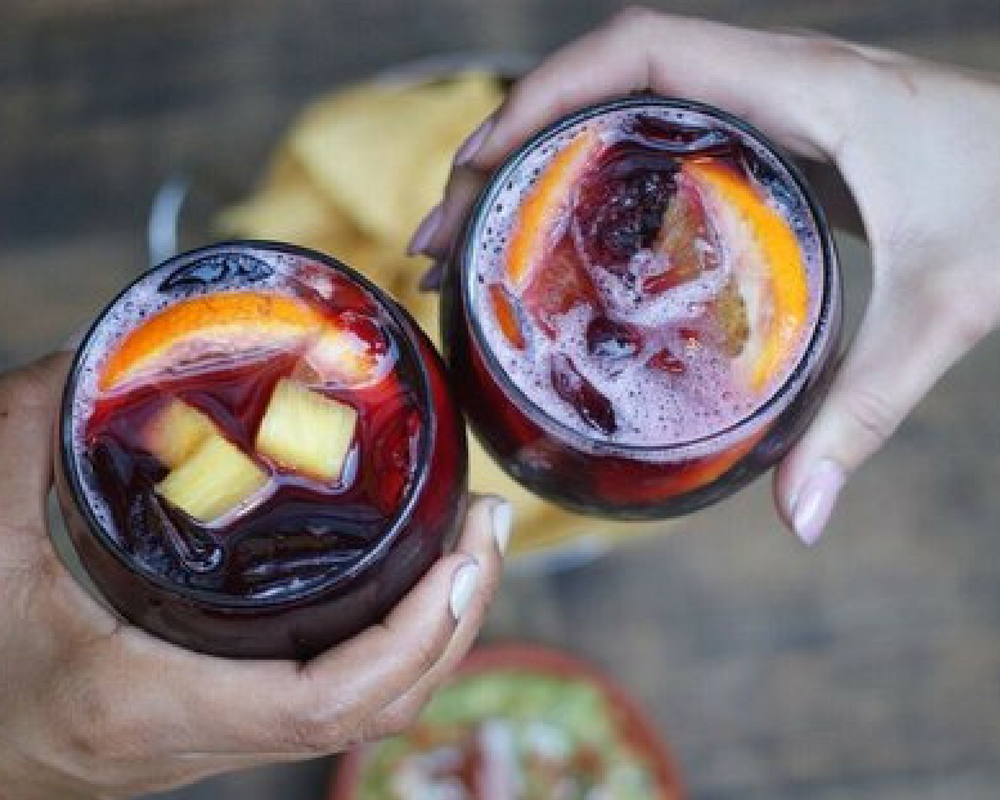 Two People Cheersing Glasses of Red Sangria
