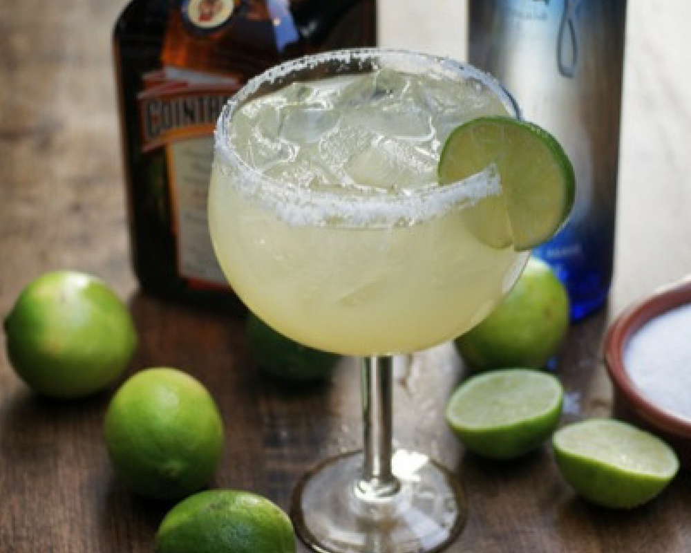 Grande Classic Margarita With Limes, Salt & Bottles of Tequila In The Background.