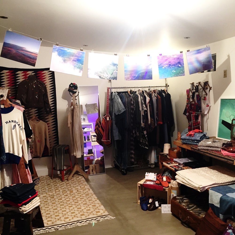 Photo Journalist and Artist Yvette Hammond's prints hanging across the pop up space, along with Mill Blu Denim Coveralls, No Grand Rituals Vintage Collection, Moon Tribe Vintage , Old Lady Baby chokers, and upcycled shoes by Caique Shoes made from rejected airplane tires