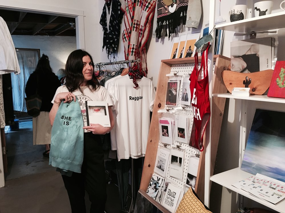 """Lauren Shapiro, Costume Designer and Wardrobe Stylist of the Late Late Show, purchases a hard copy of Dan Monick's Psychic Windows and Masculine de La FEMME's """"SHE IS"""" vintage sweater"""