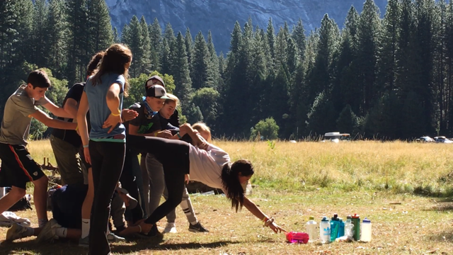 """The students took part in a """"Trust and Teamwork"""" game to """"Honor The Sages"""". The team had to work together to help each other retrieve their water bottles from the center of a giant circle without touching the HOT lava in the area inside the circle. They had to rely on each other and problem solve as a group."""