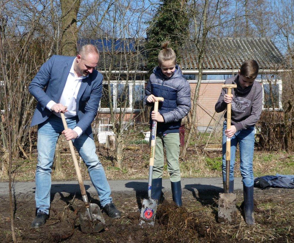 Wethouder Dennis Gudden en leerlingen van de Margrietschool planten samen elzen (foto Gemeente Wageningen).