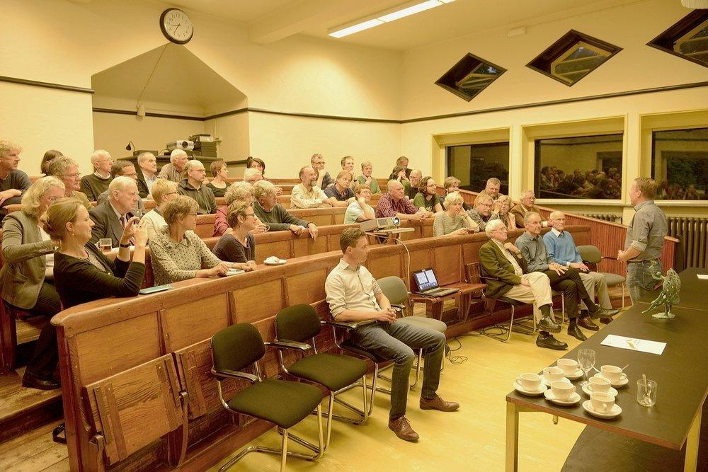 Leden en bestuur van vereniging Mooi Wageningen. Met beeld van Gelderse Pauwenveer op de vergadertafel en voorzitter Patrick Jansen aan het woord (Lustrum 2017)