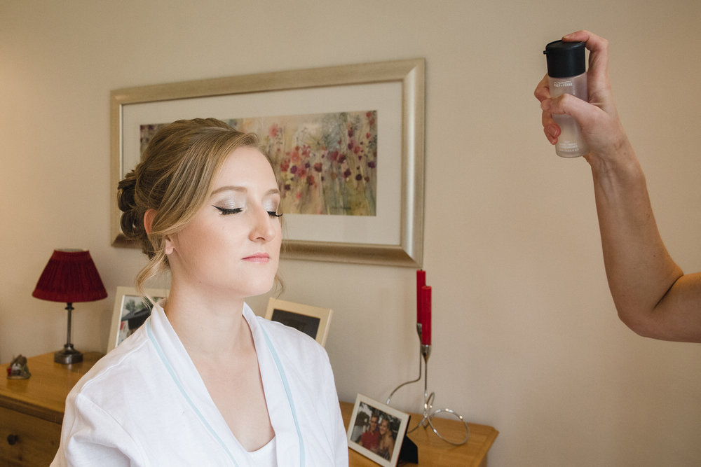 Wedding makeup artist working on bride