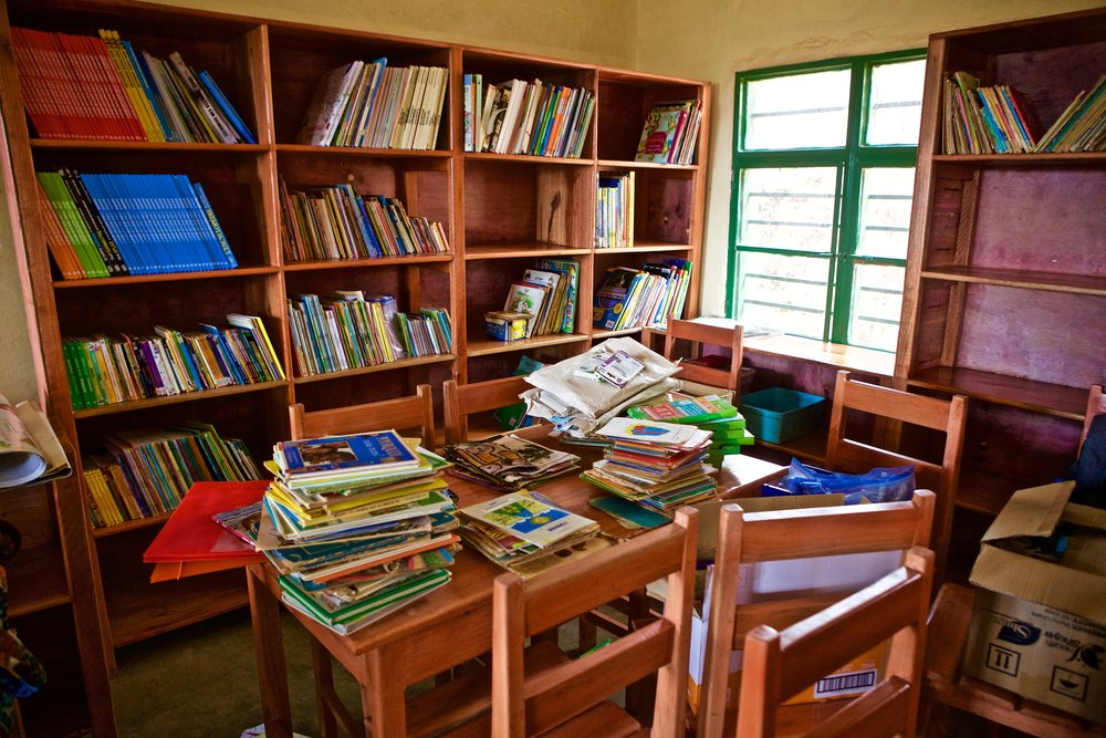 The newly constructed library being filled with books from our 2017 giving project.