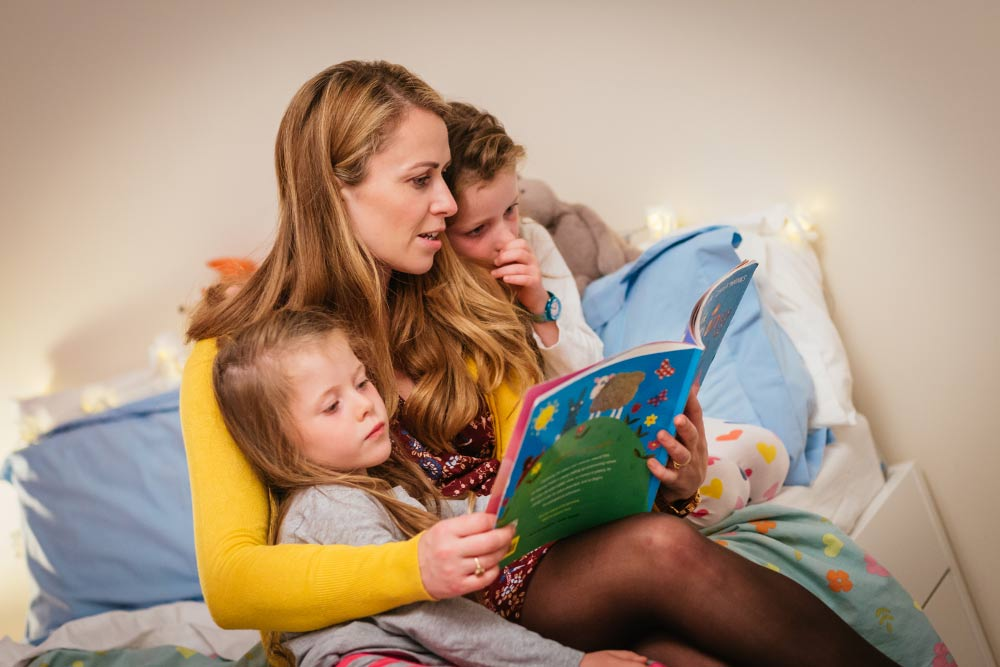 mother reading to daughters in a bedroom