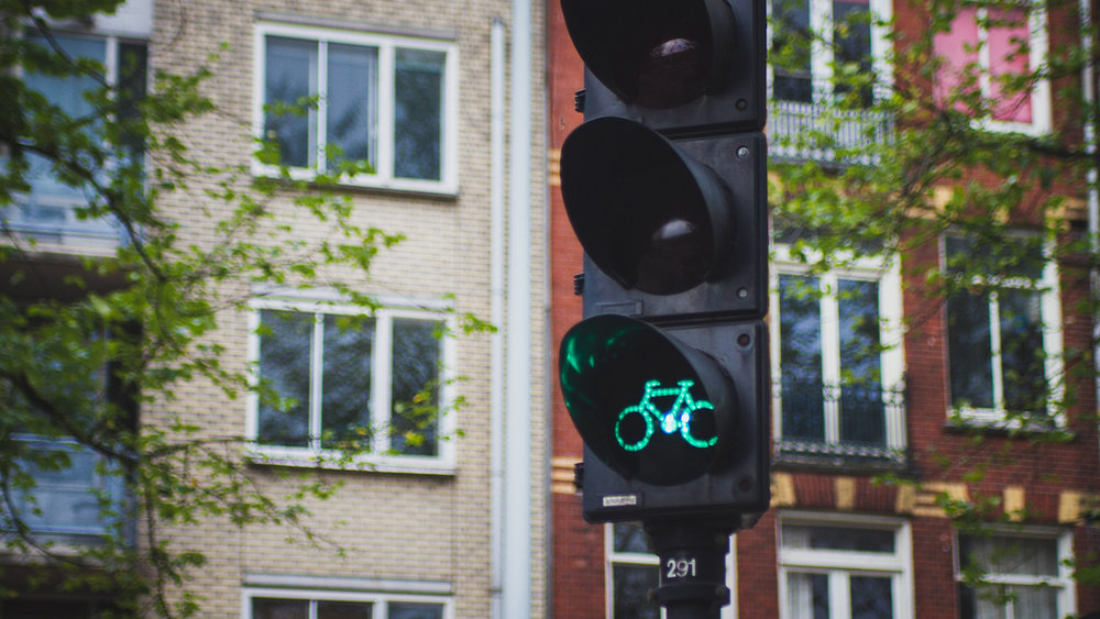 In Amsterdam, riding a bike is more common than walking or driving, so bicycles get their own paths and signals.