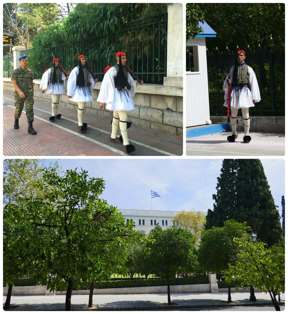 The Athens Presidential Palace is hidden behind the trees, but the Presidential Guard is more easily seen, as they're stationed on the sidewalk in front of the palace.