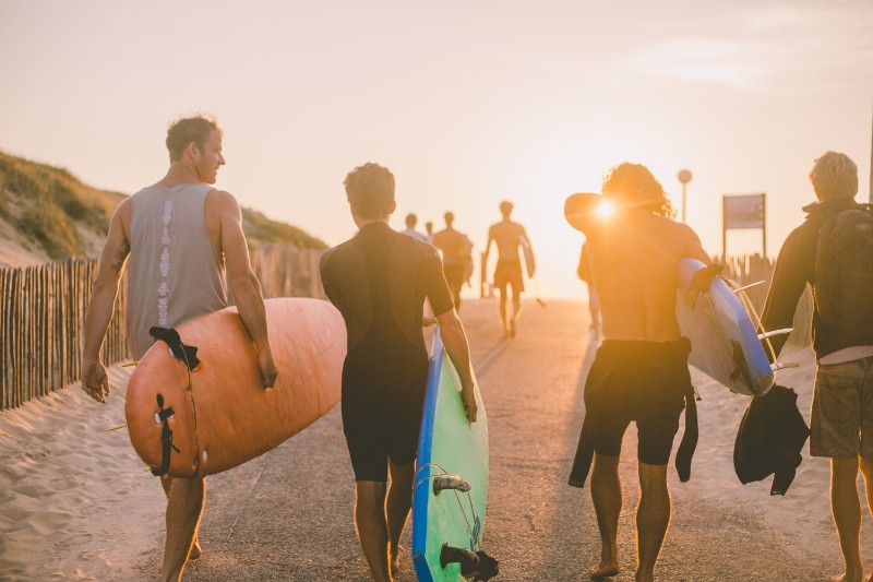group heading out for a sunset surf