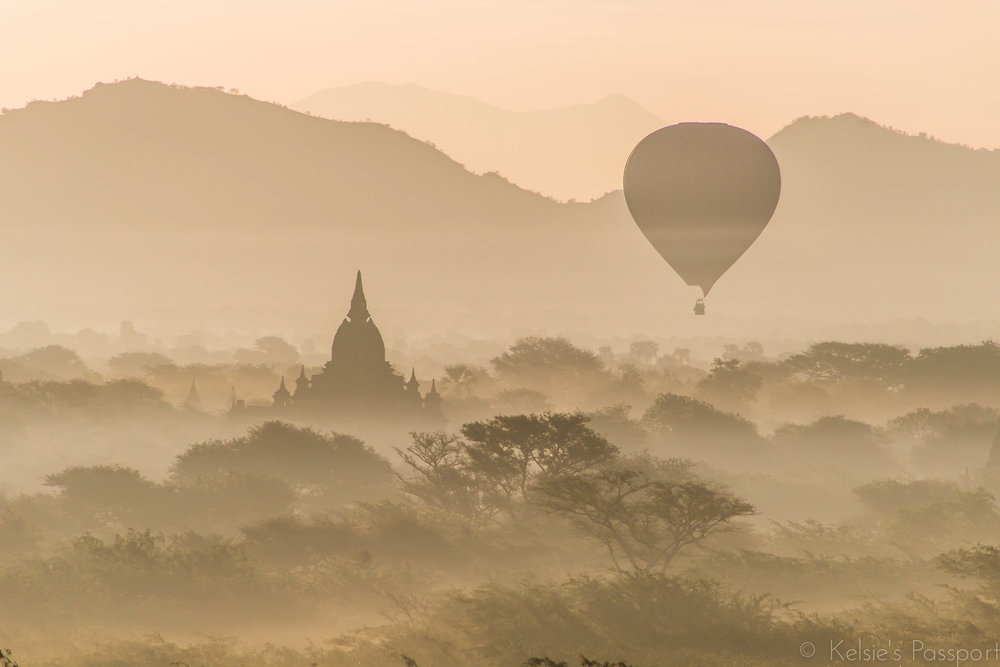 A hot air balloon dipping down into the trees and temples of Bagan.