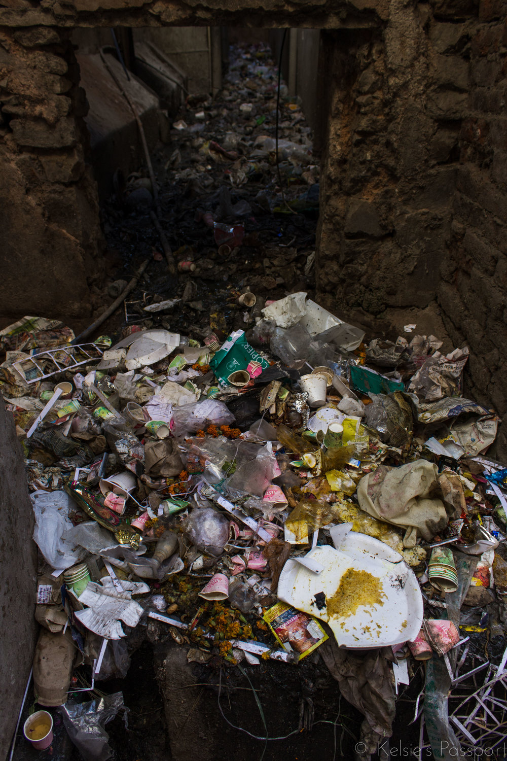 An alleyway in Jaipur overflowing with trash.